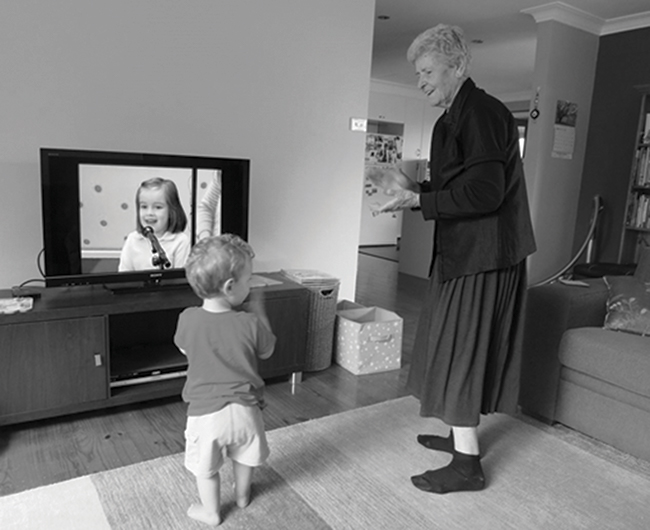 Toddler and older woman standing in front of a TV looking at each other and clapping their hands.
