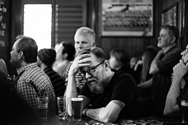Male football fan at pub with head in hands
